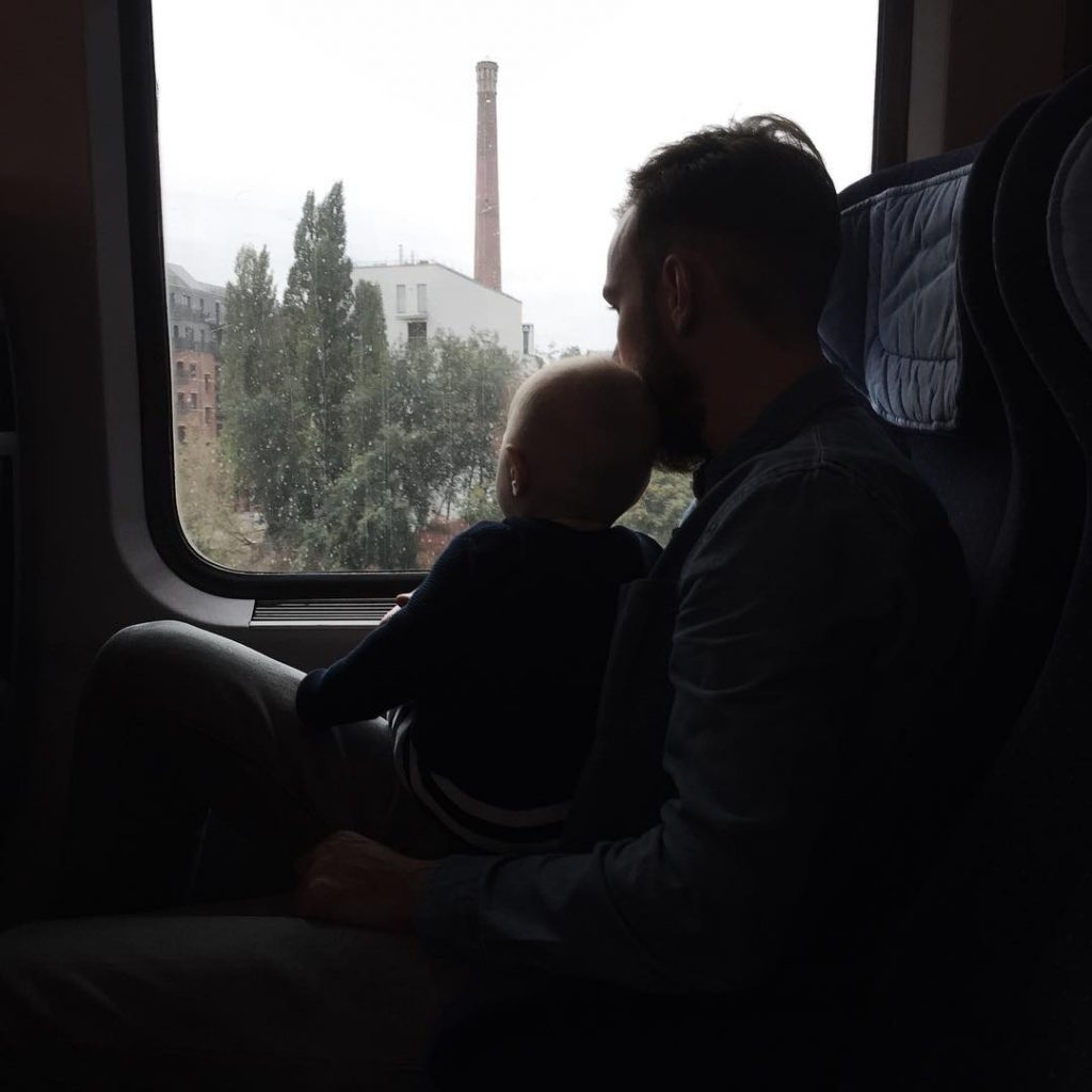 Roel van der Ven with his son on his lap looking out the train