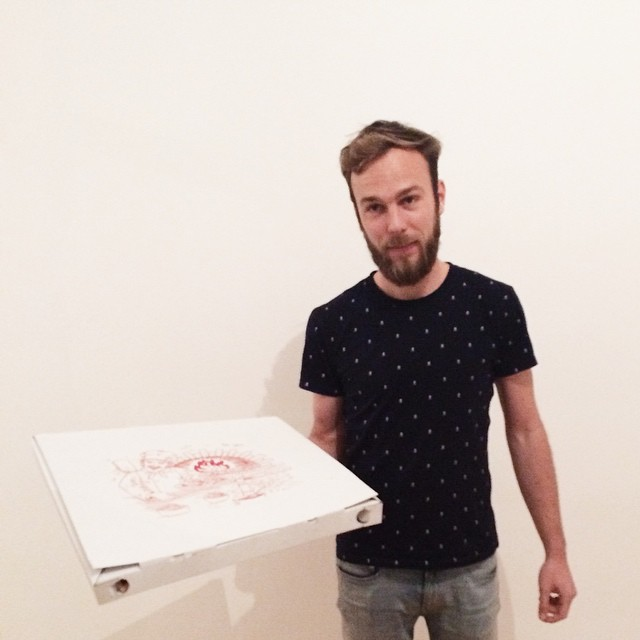 Roel van der Ven holding a pizza in their new home