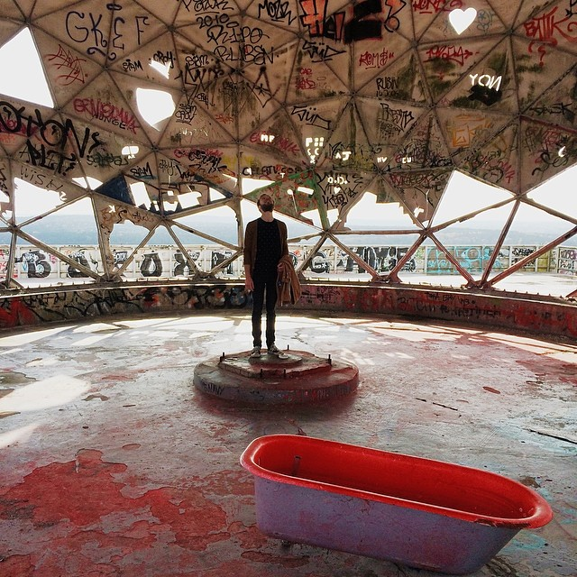 Roel standing in an abandoned listening dome with a bath tub on Teufelsberg